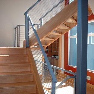 ポートランドの中サイズの木のコンテンポラリースタイルのおしゃれな折り返し階段 (木の蹴込み板、ワイヤーの手すり) の写真