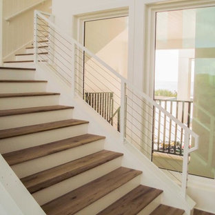 Example of a large transitional wooden l-shaped cable railing staircase design in Tampa with painted risers