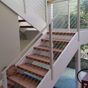 Modelo de escalera en L, actual, de tamaño medio, sin contrahuella, con escalones de madera y barandilla de cable