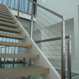 Ejemplo de escalera suspendida, actual, sin contrahuella, con escalones de madera