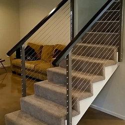 Cable Stair Railing - Powder coated steel posts with custom hardwood top rails--photo luke marshall