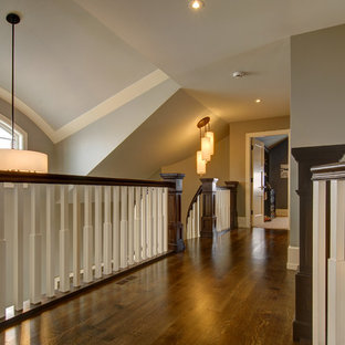 Imagen de escalera curva, de estilo americano, grande, con escalones de madera, contrahuellas de madera y barandilla de madera