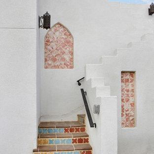 ロサンゼルスの小さいタイルのサンタフェスタイルのおしゃれな階段 (タイルの蹴込み板) の写真