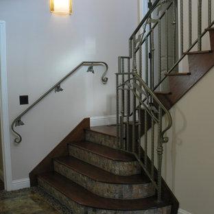 Ejemplo de escalera en U, mediterránea, grande, con escalones de madera y contrahuellas con baldosas y/o azulejos