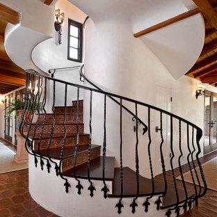На фото: изогнутая лестница в средиземноморском стиле с деревянными ступенями, подступенками из терракотовой плитки и металлическими перилами с