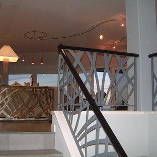 Ejemplo de escalera minimalista, de tamaño medio, con escalones con baldosas, contrahuellas con baldosas y/o azulejos y barandilla de metal