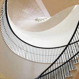 Ispirazione per una scala curva minimal di medie dimensioni con pedata in pietra calcarea, alzata in pietra calcarea e parapetto in metallo