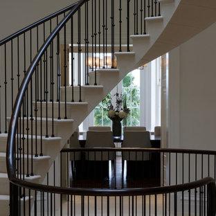 Удачное сочетание для дизайна помещения: изогнутая лестница среднего размера в современном стиле с ступенями из известняка, подступенками из известняка и металлическими перилами - самое интересное для вас