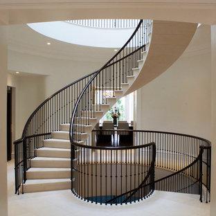 ロンドンの中サイズのライムストーンのコンテンポラリースタイルのおしゃれなサーキュラー階段 (ライムストーンの蹴込み板、金属の手すり) の写真