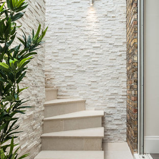 This is an example of a small contemporary curved staircase in London with tiled risers.
