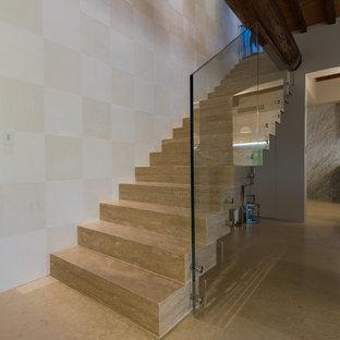 デンバーの中サイズのトラバーチンのカントリー風おしゃれなフローティング階段 (トラバーチンの蹴込み板、ガラスの手すり) の写真