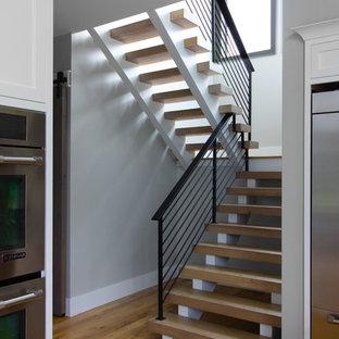 Diseño de escalera suspendida, de estilo de casa de campo, grande, con escalones de madera y barandilla de metal