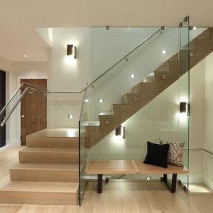 Imagen de escalera en L, contemporánea, grande, con escalones de madera, contrahuellas de madera y barandilla de vidrio