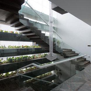 Modelo de escalera en U, actual, con escalones de mármol, contrahuellas de mármol y barandilla de vidrio
