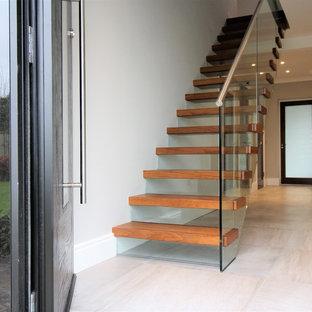 ダブリンの中サイズの木のモダンスタイルのおしゃれな直階段 (ガラスの蹴込み板) の写真