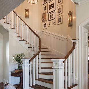 Ejemplo de escalera curva, marinera, grande, con escalones de madera y contrahuellas de madera