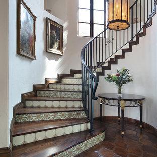 Inspiration för en stor medelhavsstil svängd trappa i trä, med sättsteg i kakel