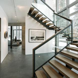 Foto de escalera moderna, sin contrahuella, con escalones de madera y barandilla de vidrio