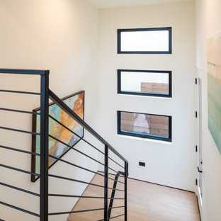 Mid-sized minimalist wooden u-shaped metal railing staircase photo in San Diego with wooden risers