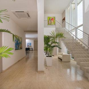 他の地域のコンクリートのコンテンポラリースタイルのおしゃれな階段 (コンクリートの蹴込み板、ワイヤーの手すり) の写真
