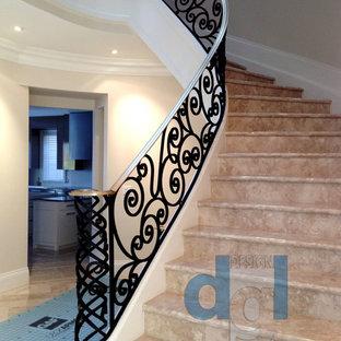 トロントの広い大理石のモダンスタイルのおしゃれなサーキュラー階段 (大理石の蹴込み板、金属の手すり) の写真