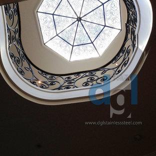 トロントの大きい大理石のモダンスタイルのおしゃれなサーキュラー階段 (大理石の蹴込み板、金属の手すり) の写真