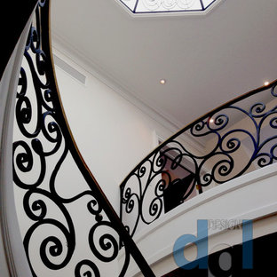 Large minimalist marble curved metal railing staircase photo in Toronto with marble risers
