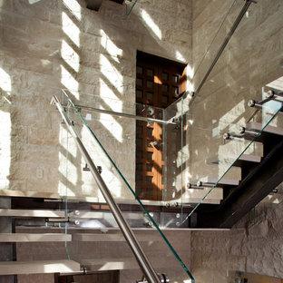Imagen de escalera en U, contemporánea, de tamaño medio, sin contrahuella, con escalones de piedra caliza y barandilla de vidrio