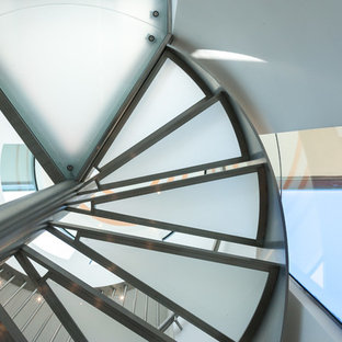 Example of a large minimalist metal spiral staircase design in San Francisco with glass risers