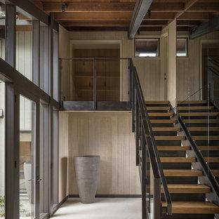 На фото: прямая лестница в стиле модернизм с деревянными ступенями, бетонными подступенками и стеклянными перилами