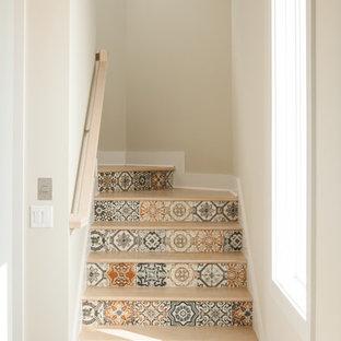Foto de escalera curva, marinera, grande, con barandilla de madera, escalones de madera y contrahuellas con baldosas y/o azulejos