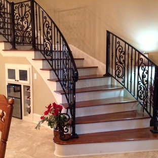 Staircase - large traditional wooden curved metal railing staircase idea in New Orleans with painted risers