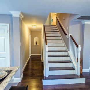 Ejemplo de escalera recta, tradicional renovada, de tamaño medio, con escalones de madera, contrahuellas de madera pintada y barandilla de madera