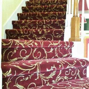 オーランドの中くらいのカーペット敷きのヴィクトリアン調のおしゃれなサーキュラー階段 (カーペット張りの蹴込み板、木材の手すり) の写真