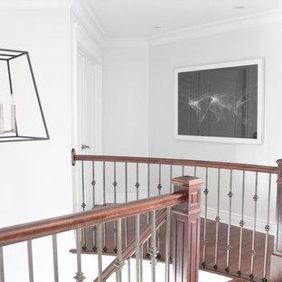 Foto de escalera curva, clásica, grande, con escalones de madera y barandilla de varios materiales