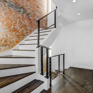 ニューヨークの中くらいのモダンスタイルのおしゃれな階段 (木の蹴込み板、金属の手すり) の写真