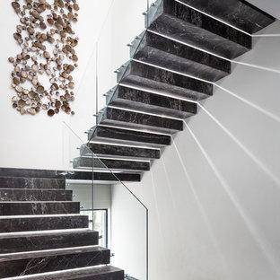 Imagen de escalera suspendida, contemporánea, sin contrahuella, con barandilla de vidrio y escalones de mármol