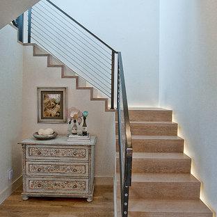 Imagen de escalera tradicional renovada con escalones de madera, contrahuellas de madera y barandilla de cable