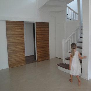 他の地域の中サイズのコンクリートのトラディショナルスタイルのおしゃれな折り返し階段 (木の蹴込み板) の写真