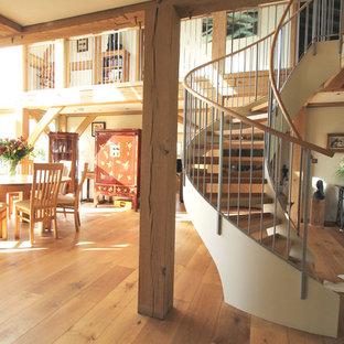 Immagine di una scala a chiocciola country con pedata in legno e nessuna alzata