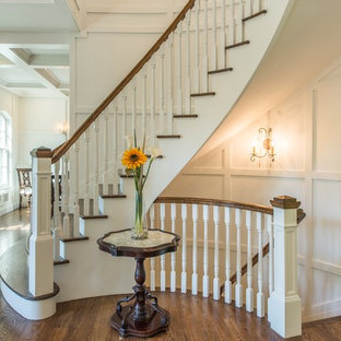 Elegant wooden curved wood railing staircase photo in New York with painted risers