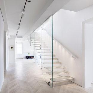 Foto di una scala sospesa design di medie dimensioni con nessuna alzata, pedata in vetro e parapetto in legno