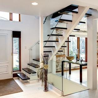 Modelo de escalera en L, minimalista, sin contrahuella, con escalones de madera y barandilla de vidrio