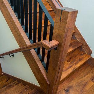 Ejemplo de escalera curva, de estilo americano, de tamaño medio, con escalones de madera, contrahuellas de madera y barandilla de varios materiales