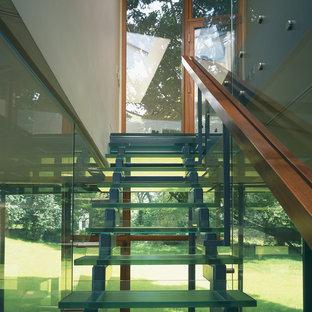 Immagine di una scala a rampa dritta design di medie dimensioni con pedata in vetro e alzata in vetro