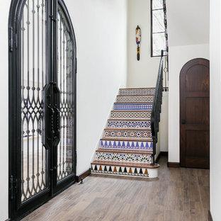 Пример оригинального дизайна: п-образная лестница среднего размера в средиземноморском стиле с деревянными ступенями, подступенками из терракотовой плитки и металлическими перилами
