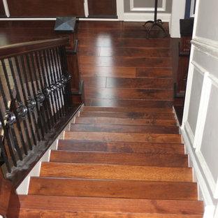フィラデルフィアの広い木のトラディショナルスタイルのおしゃれな直階段 (フローリングの蹴込み板、金属の手すり) の写真