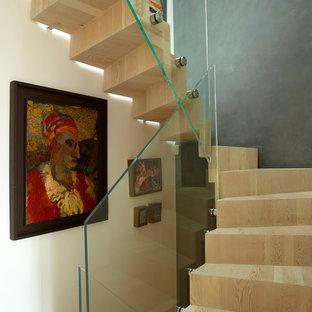 Immagine di una scala a chiocciola contemporanea di medie dimensioni con pedata in legno, alzata in legno e parapetto in vetro