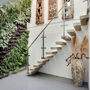 Foto de escalera recta, actual, de tamaño medio, sin contrahuella, con escalones de hormigón y barandilla de vidrio