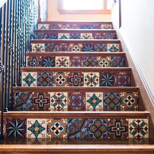 Diseño de escalera recta, de estilo americano, grande, con escalones de madera, contrahuellas con baldosas y/o azulejos y barandilla de varios materiales
